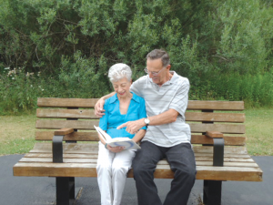 A resident at Eden Heights of West Seneca in Buffalo looks through a photo album with a visitor.