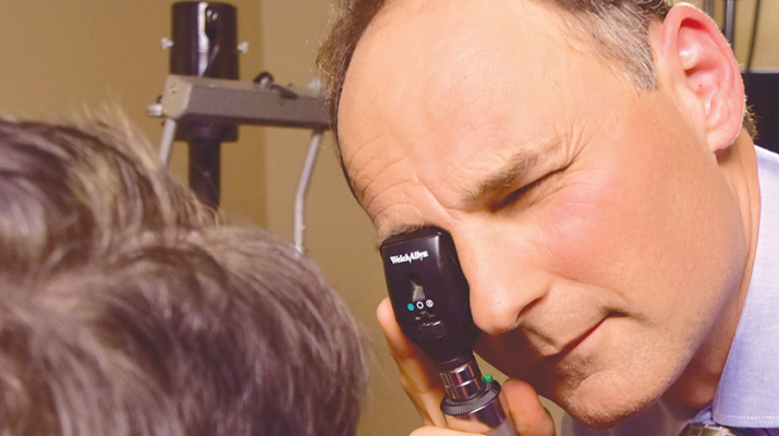 David P. Montesanti, a board-certified surgeon with Eye Care & Vision Associates, uses an ophthalmoscope to examine a patient's eyes.