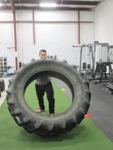Impact Fitness in Hamburg offers a variety of option for exercise and fitness, including battle ropes, Jacob's ladder and tire-flipping. Shown is strength trainer Chris Cammarata demonstrating tire flipping.