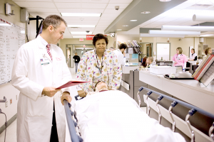 """Physician Michael Manka, chief of emergency medicine at ECMC, escorts a patient on gurney. """"Almost all the major trauma injuries tend to come to ECMC because we are the only adult trauma center in Western New York,"""" he says."""