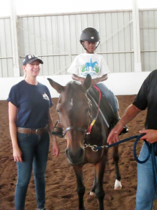 Jennifer Hemingway, an instructor with Buffalo Therapeutic Riding Center, helps 7-year-old Sammy ride one of the horses at the center.