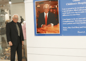 Salvatore standing near a plaque at the John R. Oishei Children's Hospital. All TV sets at the children's hospital were donated by him.
