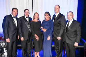 Honored for their distinguished service during Springfest 2019 are physician Thom R. Loree, (second from left); dentist Maureen Sullivan, (third from left); nurse Donna Oddo, (third from right); and Jim Kelly (second from right). Posing with the honorees are ECMC Corp. President & CEO Thomas J. Quatroche Jr., (left) and ECMC Corp. Board of Directors Chairman Jonathan A. Dandes (right).