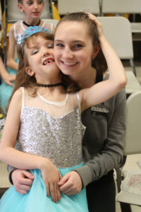 The bond between dancers and volunteers is strong, as shown here as Aria Lewis and Jillian Szeluga embrace before they hit the stage.