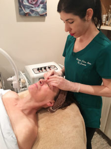 """Janine Testa, owner of Holistic Skin Care by Janine in Williamsville, applying a charcoal mask on a client's face. """"It's good for people who have clogged pores, blackheads and oily skin. It's good for acne. But they can be drying."""""""