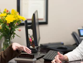 Laura K. Fisher, right, talks to a patient at Windsong, which offers radiology, genetic counseling, vein care and breast care in Williamsville. Fisher is a certified genetic counselor and director of genetic counseling at Windsong.
