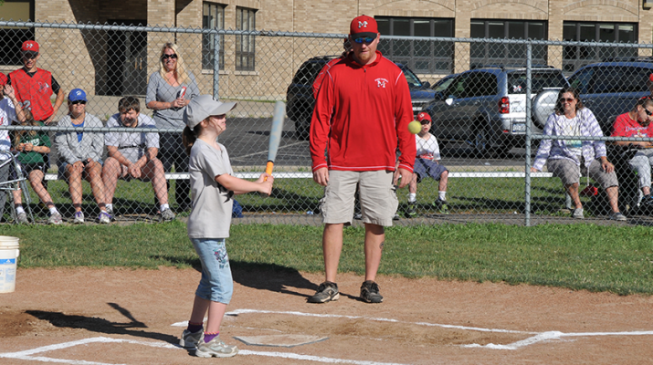 """One of the unique aspects of challenger baseball is the use of the """"buddy system,"""" in which older children and young adults who play baseball in other leagues provide assistance at the plate and in the field."""