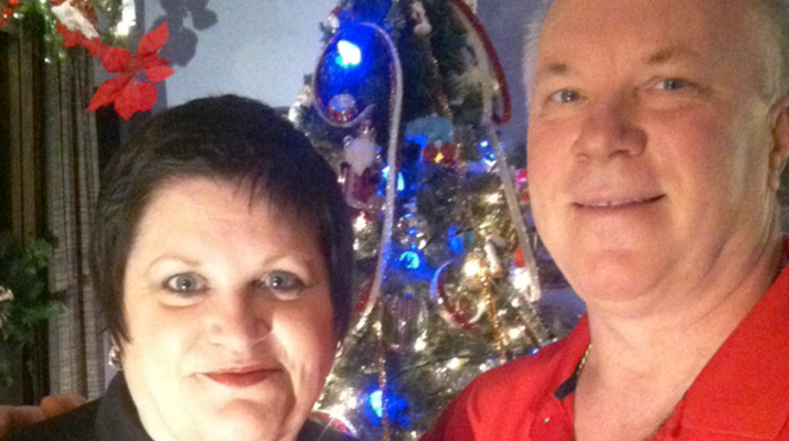 Charise and her oldest brother, David Nowatzki, standing by their Christmas tree