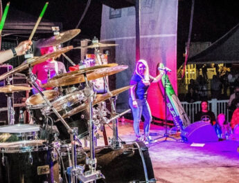 Sonny Muscato plays drums with Emily Styn in the background and Max Muscato playing guitar at the Rock Autism Music Festival.